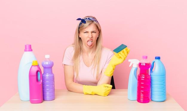 Jeune femme blonde se sentant dégoûtée et irritée et tirant la langue. concept de femme de ménage