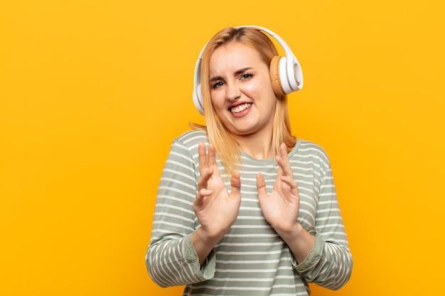 Jeune femme blonde se sentant dégoûtée et nauséeuse, s'éloignant de quelque chose de méchant, malodorant ou puant, disant beurk