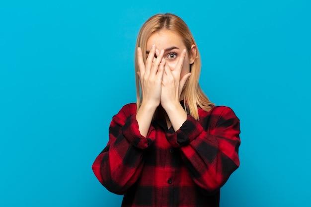 Jeune femme blonde se sentant effrayée ou gênée, jetant un coup d'œil ou espionnant les yeux à moitié couverts de mains