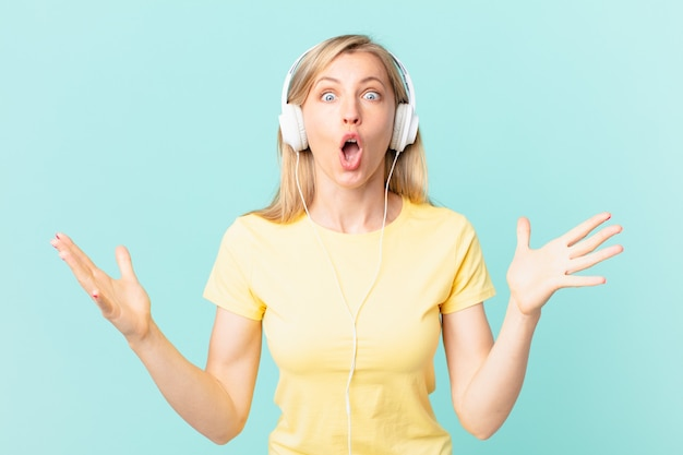 Jeune femme blonde se sentant extrêmement choquée et surprise et écoutant de la musique.