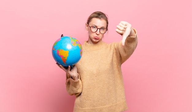 Jeune femme blonde se sentant fâchée, en colère, agacée, déçue ou mécontente, montrant les pouces vers le bas avec un regard sérieux. notion de monde