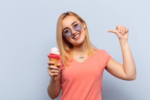 Jeune femme blonde se sentant fière, arrogante et confiante, à la satisfaction et au succès, pointant vers soi