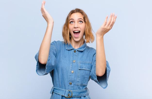 Jeune femme blonde se sentant heureuse, étonnée, chanceuse et surprise, célébrant la victoire avec les deux mains en l'air contre le mur de couleur plat