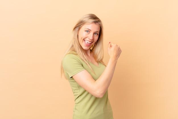 Jeune femme blonde se sentant heureuse et faisant face à un défi ou célébrant