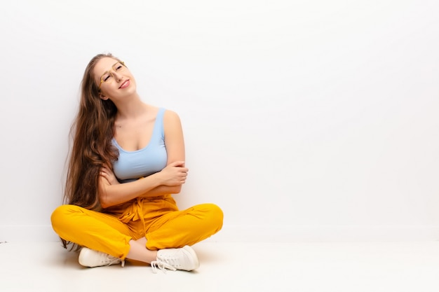 Jeune femme blonde se sentant heureuse, fière et pleine d'espoir, se demandant ou pensant, levant les bras croisés assis sur le sol