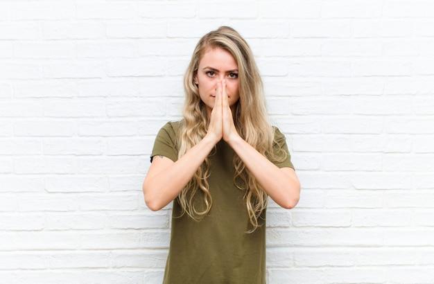 Jeune femme blonde se sentant inquiète, pleine d'espoir et religieuse, priant fidèlement avec les paumes pressées, demandant pardon contre le mur de briques