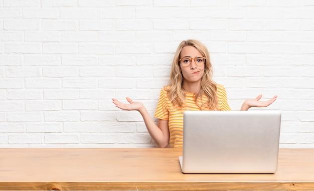 Jeune femme blonde se sentant perplexe et confuse, doutant, pondérant ou choisissant différentes options avec une drôle d'expression à l'aide d'un ordinateur portable
