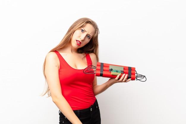 Jeune femme blonde se sentant perplexe et confuse, avec une expression stupide et stupéfaite regardant quelque chose d'inattendu tenant une bombe de dynamite