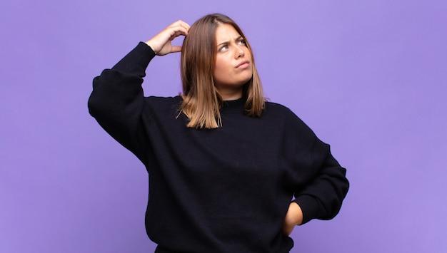 Jeune femme blonde se sentant perplexe et confuse, se grattant la tête et regardant sur le côté