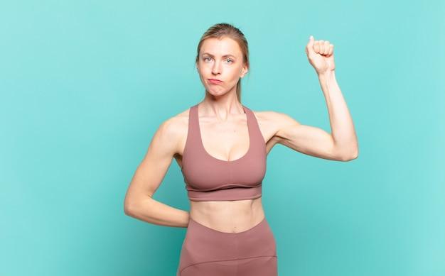 Jeune femme blonde se sentant sérieuse, forte et rebelle, levant le poing, protestant ou luttant pour la révolution. notion de sport