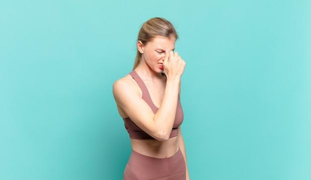 Jeune femme blonde se sentant stressée, malheureuse et frustrée, touchant le front et souffrant de migraine de violents maux de tête. notion de sport