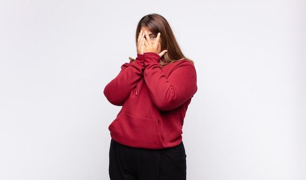 Jeune femme blonde se sentir effrayée ou embarrassée, furtivement ou espionnage avec les yeux à moitié couverts de mains