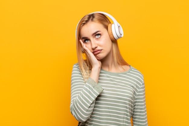 Jeune femme blonde se sentir ennuyé, frustré et somnolent après une tâche ennuyeuse, terne et fastidieuse, tenant le visage avec la main