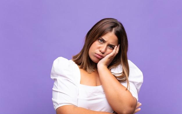 Jeune femme blonde se sentir ennuyé, frustré et somnolent après une tâche fatigante, terne et fastidieuse, tenant le visage avec la main