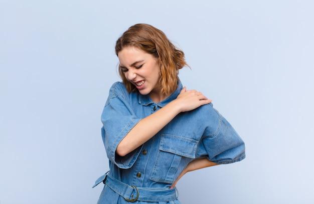 Jeune femme blonde se sentir fatiguée, stressée, anxieuse, frustrée et déprimée, souffrant de douleurs au dos ou au cou contre un mur de couleur plat