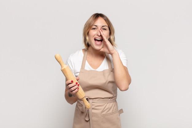 Jeune femme blonde se sentir heureuse, excitée et positive, donnant un grand cri avec les mains à côté de la bouche, appelant
