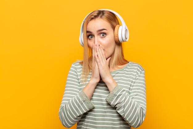Jeune Femme Blonde Se Sentir Inquiet, Bouleversé Et Effrayé, Couvrant La Bouche Avec Les Mains, L'air Anxieux Et Ayant Foiré Photo Premium