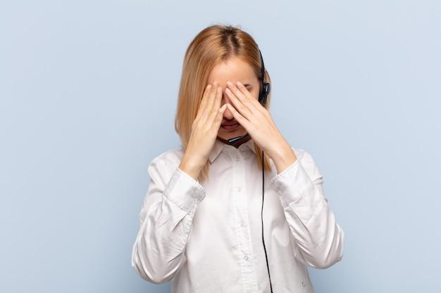 Jeune femme blonde se sentir triste, frustré, nerveux et déprimé, couvrant le visage à deux mains, pleurant
