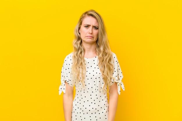 Jeune femme blonde se sentir triste et pleurnicher avec un regard malheureux, pleurer avec une attitude négative et frustrée sur le mur jaune