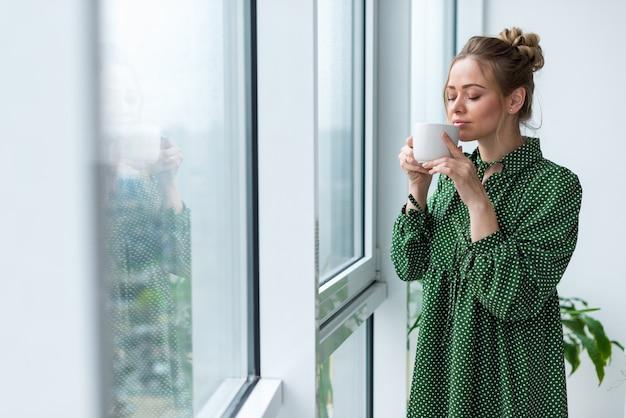 Jeune femme blonde se tient dans la salle tenant une tasse et sentant aromat de boisson