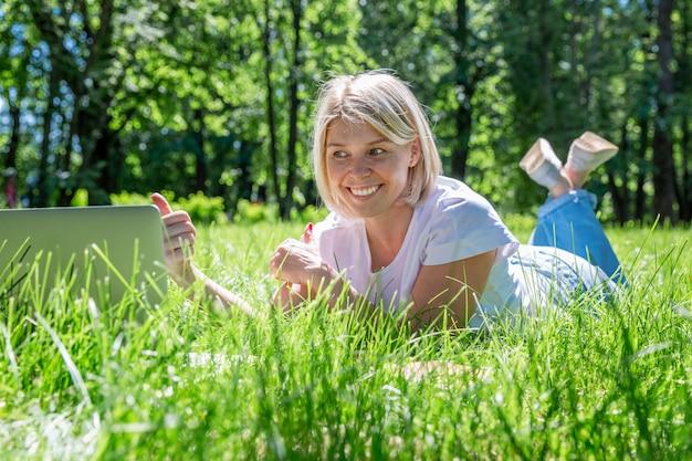 Jeune femme blonde se trouve dans un parc sur l'herbe avec un ordinateur portable. blog, éducation et télétravail.