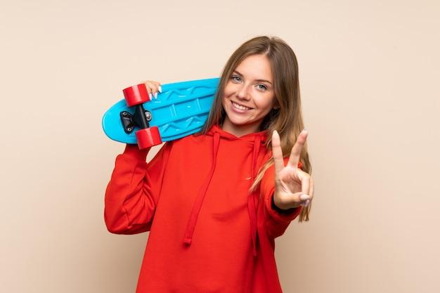 Jeune femme blonde avec skate et geste de victoire