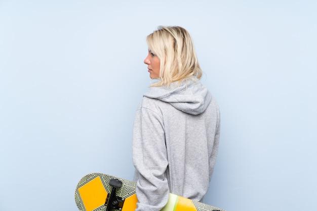 Jeune femme blonde avec skate en position arrière