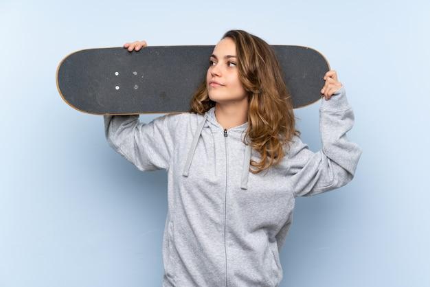 Jeune femme blonde avec skate et à la recherche de côté