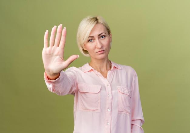 Jeune femme blonde slave montrant le geste d'arrêt