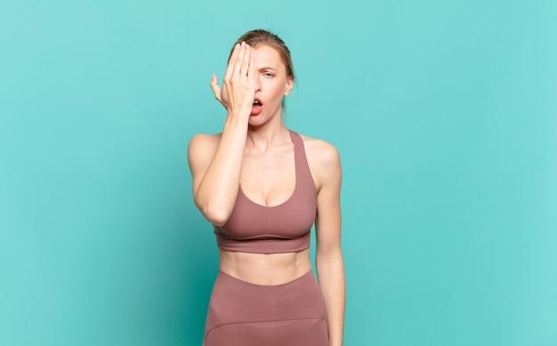 Jeune femme blonde à la somnolence, s'ennuie et bâille, avec un mal de tête et une main couvrant la moitié du visage. notion de sport