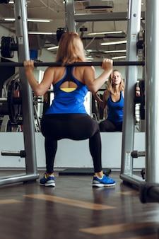 Jeune femme blonde soulevant des haltères dans la salle de sport