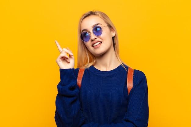 Jeune femme blonde souriant joyeusement et regardant sur le côté