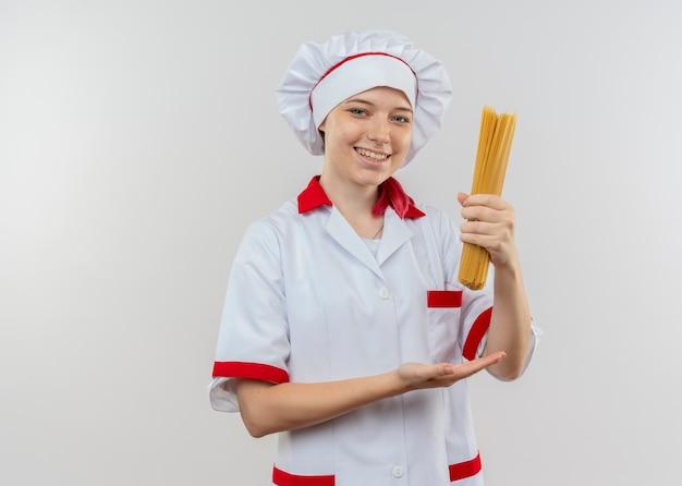Jeune femme blonde souriante chef en uniforme de chef détient bouquet de spaghettis isolé sur mur blanc