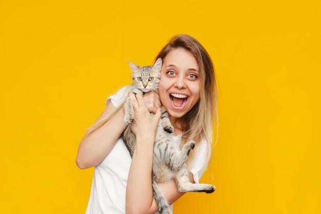 Une jeune femme blonde souriante excitée assez caucasienne dans un t-shirt blanc avec un chat dans ses mains est heureuse de la nouvelle isolée sur un mur jaune de couleur vive