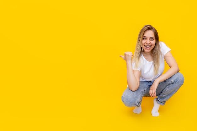 Une jeune femme blonde souriante excitée caucasienne assise sur ses hanches pointant un espace vide vide pour le texte ou la conception avec son doigt présentant le produit isolé sur un mur jaune de couleur vive