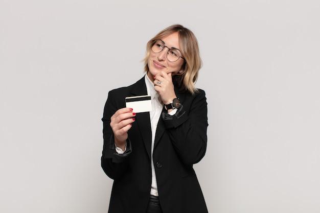 Jeune femme blonde souriante avec une expression heureuse et confiante avec la main sur le menton, se demandant et regardant sur le côté