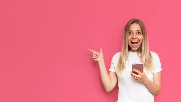 Une jeune femme blonde souriante impressionnée par un t-shirt blanc copie un espace vide pour le texte ou la conception avec son doigt tenant un téléphone portable isolé sur un mur rose de couleur vive