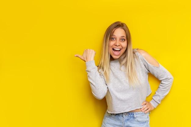 Une jeune femme blonde souriante impressionnée de race blanche dans des vêtements décontractés indique un espace vide vide pour le texte ou la conception avec son doigt présentant un produit isolé sur un mur jaune de couleur vive