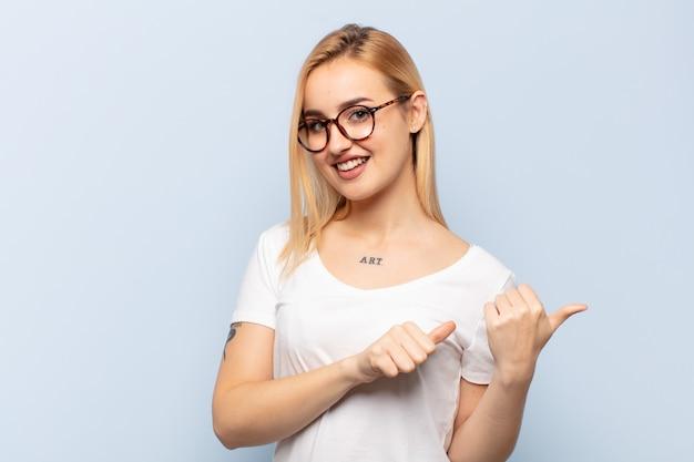 Jeune femme blonde souriante joyeusement et désinvolte pointant vers l'espace de copie sur le côté, se sentant heureuse et satisfaite