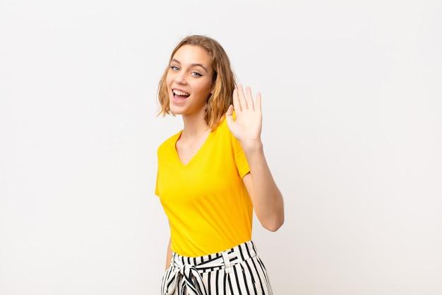 Jeune femme blonde souriante joyeusement et joyeusement, agitant la main, vous accueillant et vous saluant, ou disant au revoir contre un mur de couleur plat