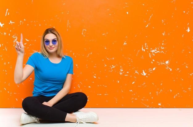 Jeune femme blonde souriante joyeusement et joyeusement, pointant vers le haut avec une main pour copier l'espace assis sur le sol