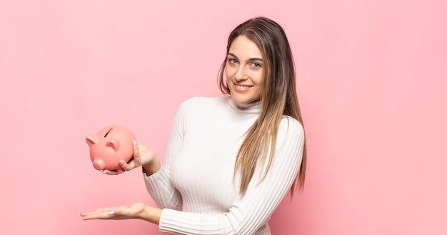 Jeune femme blonde souriante joyeusement, se sentant heureuse et montrant un concept dans l'espace de copie avec la paume de la main