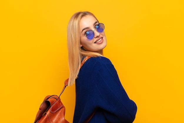 Jeune femme blonde souriante joyeusement, se sentant heureuse, satisfaite et détendue, les bras croisés et regardant sur le côté