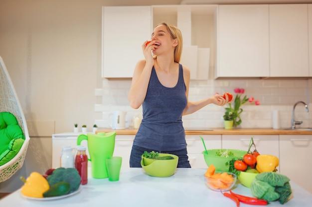 Jeune femme blonde souriante mord la tomate biologique lors de la cuisson des fruits frais dans la cuisine. alimentation équilibrée. la nourriture végétarienne. détox de régime