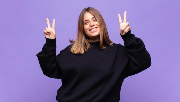 Jeune femme blonde souriante et à la recherche de bonheur, sympathique et satisfait, gesticulant la victoire ou la paix à deux mains