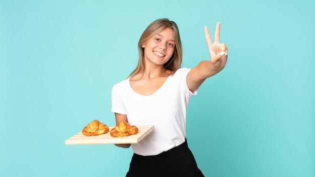 Jeune femme blonde souriante et semblant amicale, montrant le numéro deux et tenant un plateau à croissants