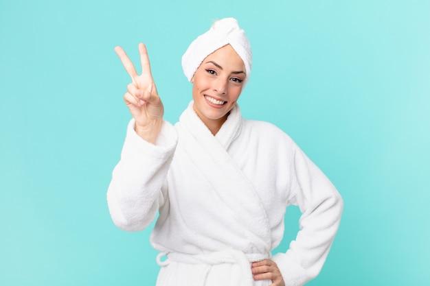 Jeune femme blonde souriante et semblant heureuse, gesticulant la victoire ou la paix. notion de douche.