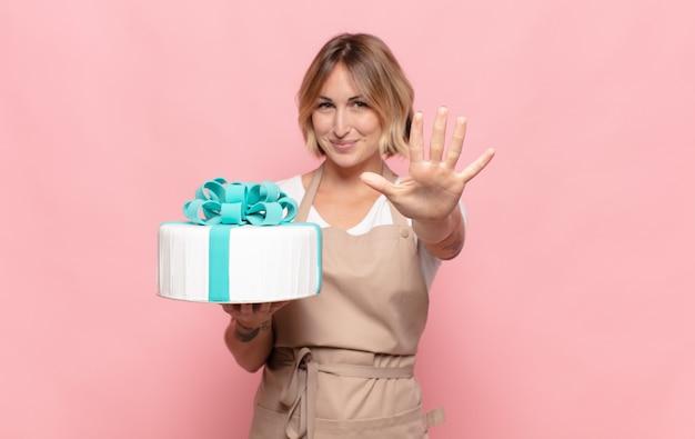 Jeune femme blonde souriante et à la sympathique, montrant le numéro cinq ou cinquième avec la main en avant, compte à rebours