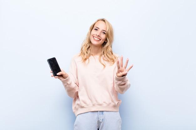 Jeune femme blonde souriante et à la sympathique, montrant le numéro quatre ou quatrième avec la main vers l'avant, compte à rebours à l'aide d'un smartphone