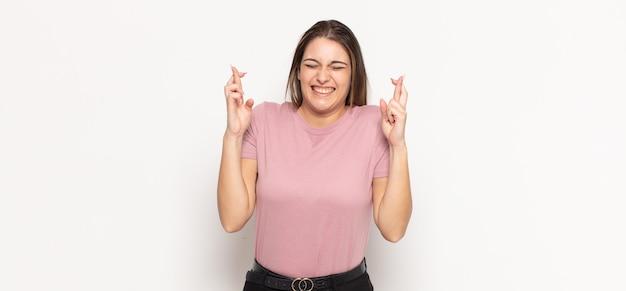 Jeune femme blonde souriante et traversant anxieusement les deux doigts, se sentant inquiète et souhaitant ou espérant avoir de la chance